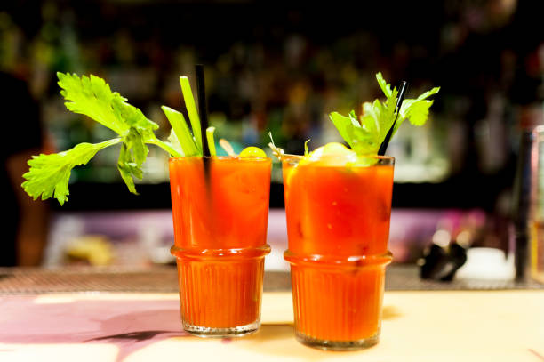couple of intense red bloody mary cocktails on inside bar on glasses with fresh green celeries, symbol of nightlife stock photo