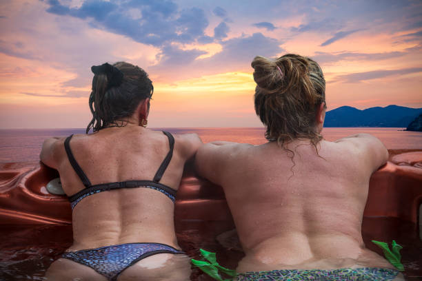 couple of ladies enjoying benefits of the hot tub couple of ladies on vacations having fun and enjoying the benefits of the outdoor hot tub in front of sunset middle aged women in bikinis stock pictures, royalty-free photos & images