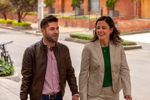A Couple Of Latin American Colleagues Are Seen Walking Down The Sidewalk On A Sunny Afternoon, Chatting With Each Other; She Is Formally Dressed While He Is In Casual Clothing. Horizontal Format. stock photo