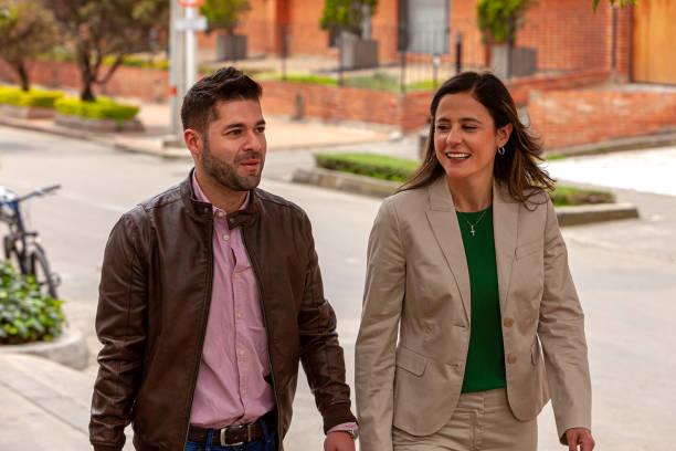 Ein paar lateinamerikanische Kollegen werden gesehen, wie sie an einem sonnigen Nachmittag den Bürgersteig hinuntergehen und miteinander plaudern; Sie ist formell gekleidet, während er in lässiger Kleidung ist. Horizontales Format. – Foto