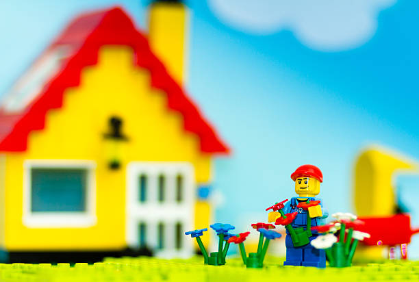 couple of lego mini figure planting flowers in a garden. - lego house stock photos and pictures