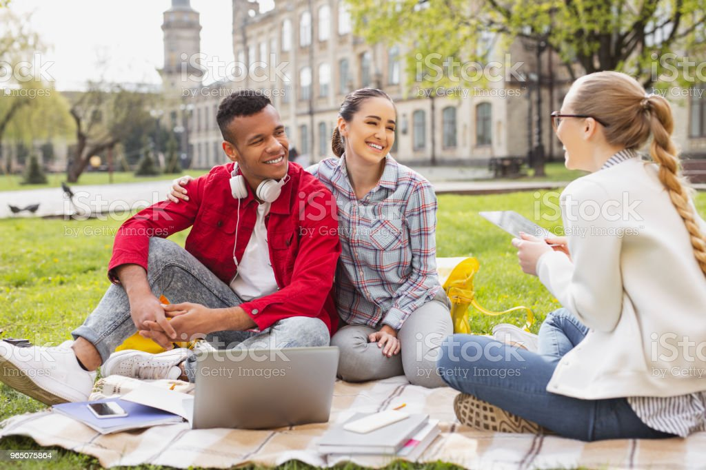 Couple of lovely students sitting in front of their mutual friend royalty-free stock photo