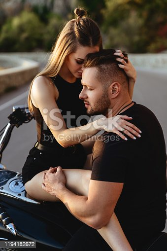 Couple of lovers kissing and hugging on motorbike - Two bikers stop in the countryside