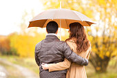 Young couple man and woman walking under the umbrella, turn back, rainy autumn cold day in the park. First date, love, relationships.