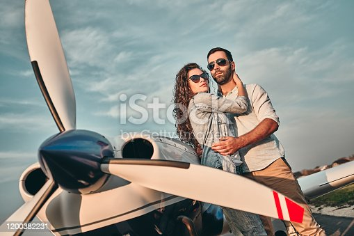 Couple of lovers taking a charter airplane. Tourists on vacation waiting their flight to go on excursion