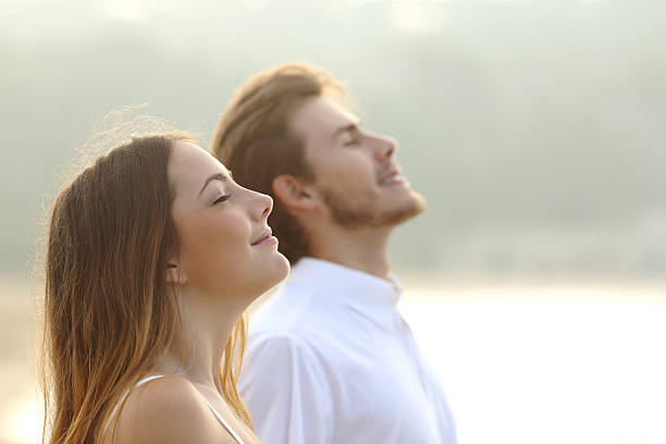 Couple of man and woman breathing deep fresh air stock photo