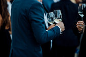 Couple of man  with a glass of wine at social event wearing elegant cloth.