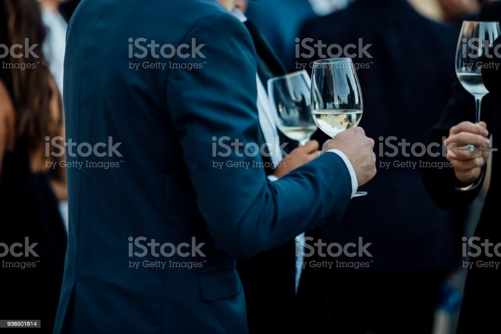Couple of man  with a glass of wine at social event wearing elegant cloth. stock photo