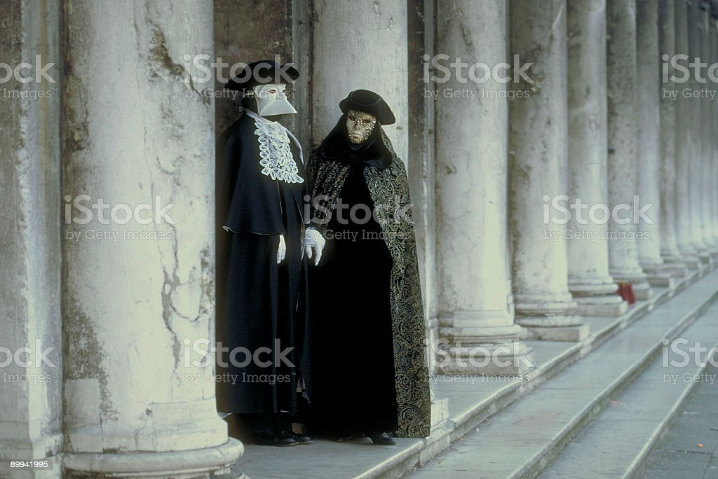 Couple of masks between columns in Venice royalty-free stock photo
