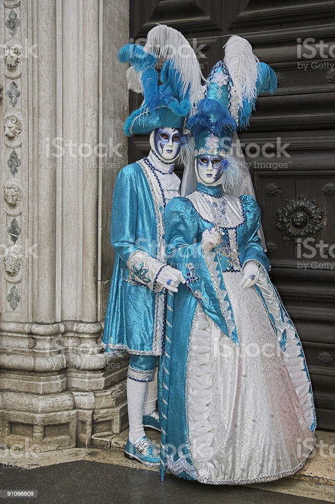 Couple of masks with elegant costumes at carnival in Venice royalty-free stock photo
