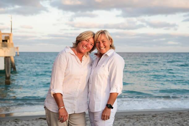 Couple of mature LGBTQ women posing on the beach. stock photo