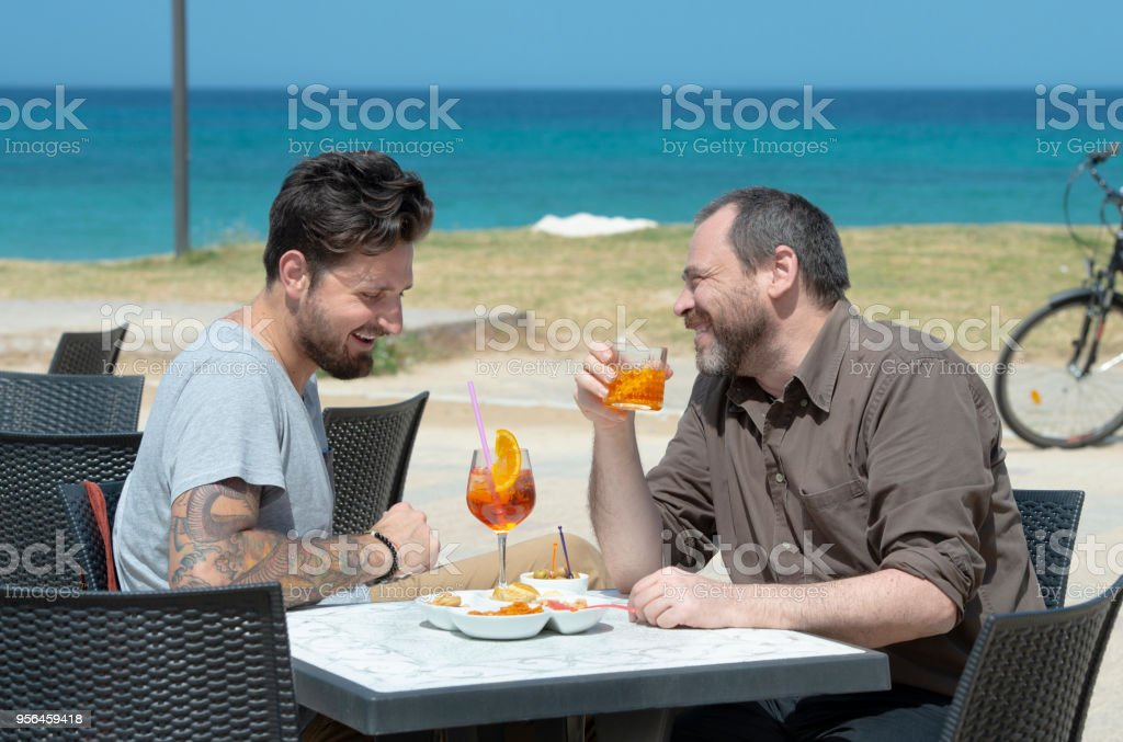 Couple of men take an appetizer at the bar - foto stock