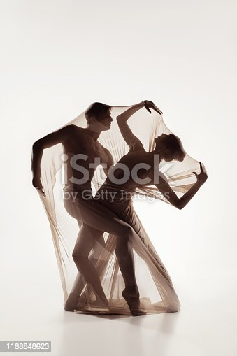 Elegance. Couple of modern ballet dancers isolated on white background. Contemporary art ballet. Young flexible athletic man and woman in fabric. Grace, motion, flexibility, inspiration concept.