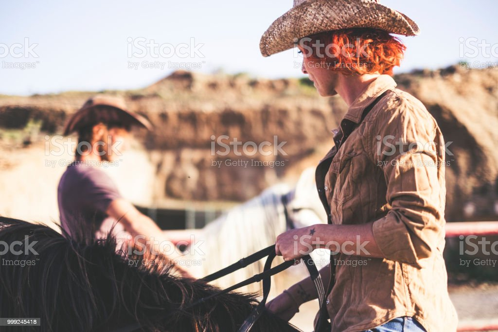 couple of modern cowboy ride together. one man and one woman with two...