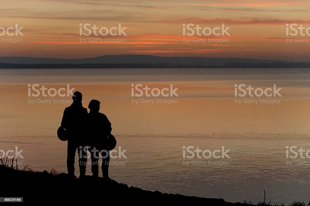 Couple of motorbikers lakeside watching sunset cloudscape (XXL) royalty-free stock photo