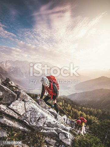 Couple climbing via ferrata, a secure climbing route found in Alps. Alpine climbing on a sunny day in the mountains. Valley covered in fog, temperature inversion in the valley.
