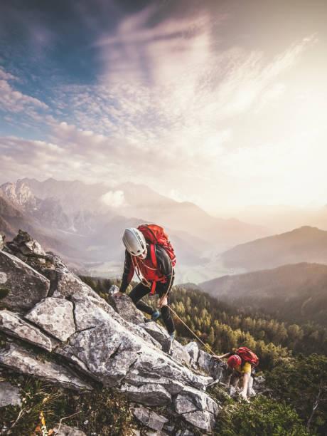 couple of mountain climbers, climbing via ferrata, a secure climbing route - alpinismo foto e immagini stock