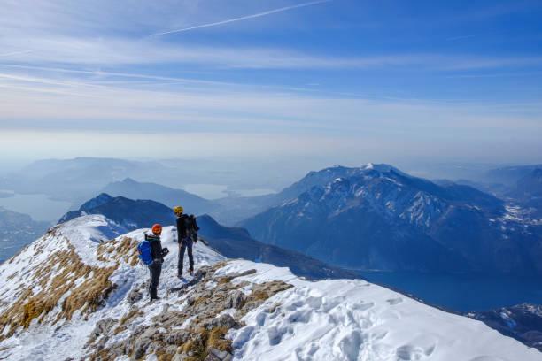 paar van bergbeklimmers op de top van de bergrug - lecco lombardije stockfoto's en -beelden