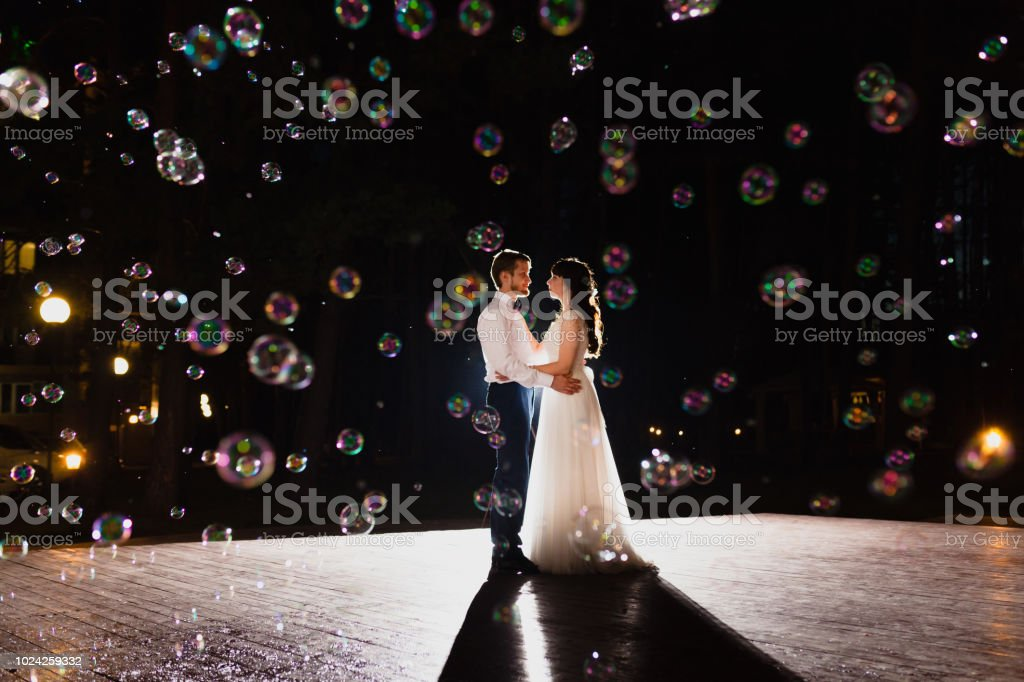 Couple of newlyweds and huge amount of bubbles are flying in the air stock photo