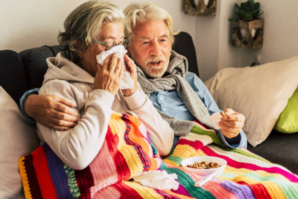 Couple of old aged senior people at home with seasonal winter cold illness disease  sit down on the sof together forever - health problems for retired man and woman with white hair stock photo