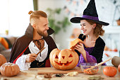 istock couple of people are preparing for Halloween in costumes of witch and vampire with pumpkins 1175403780