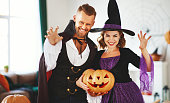 istock couple of people are preparing for Halloween in costumes of witch and vampire with pumpkins 1176427876