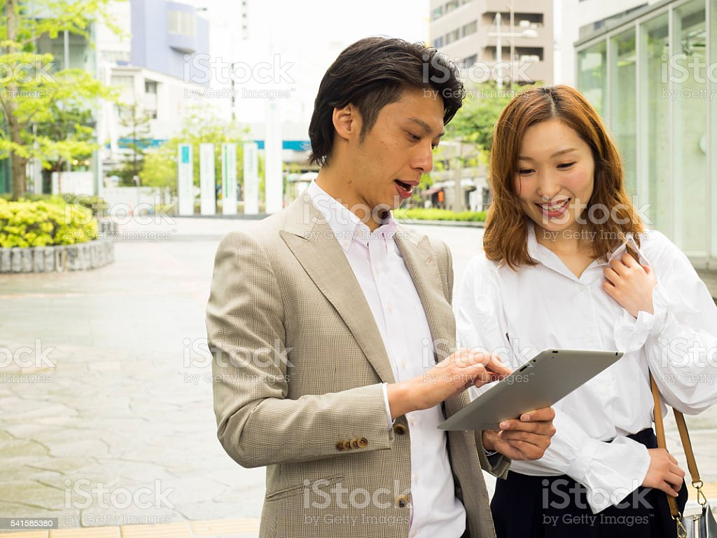 couple of people watching tablet. stock photo