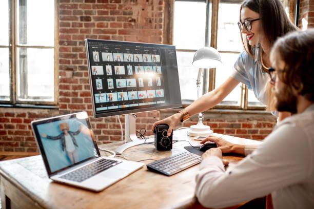 pareja de fotógrafos que trabajan en los equipos en el estudio - oficina de empleo fotografías e imágenes de stock