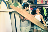 Positive couple of positive man with boards for surfing in the shop