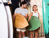 Cheerful positive couple of positive man with boards for surfing in the shop