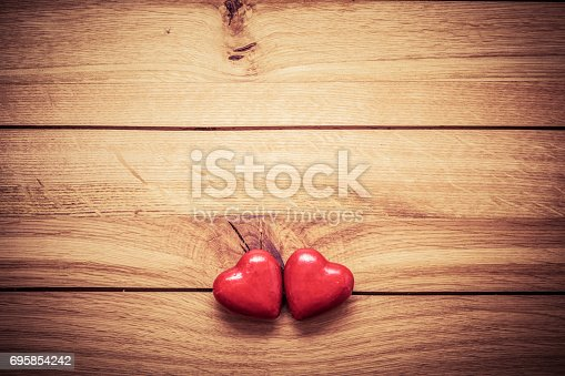istock A couple of red little hearts on wood. Vintage concept of love, Valentine's Day 695854242