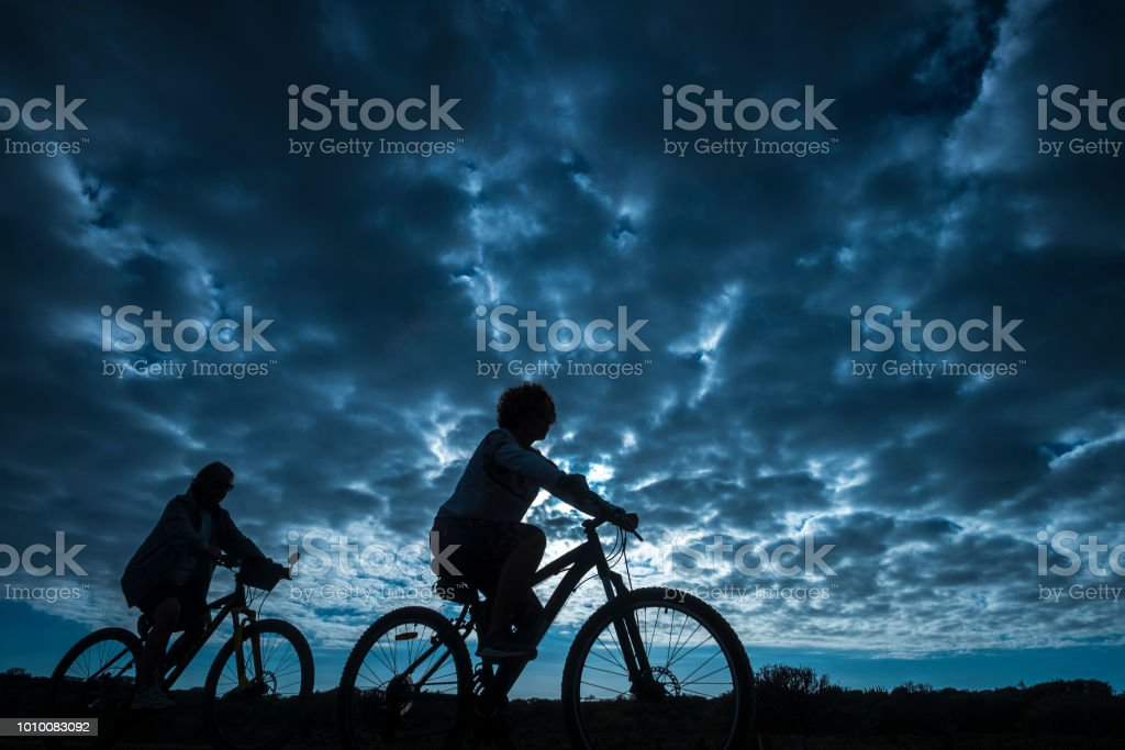 couple of rider in mountain bike come back home after a sport bikes session outdoor. beautiful blue sky with clouds in backgorund. people in silhouette in activity stock photo