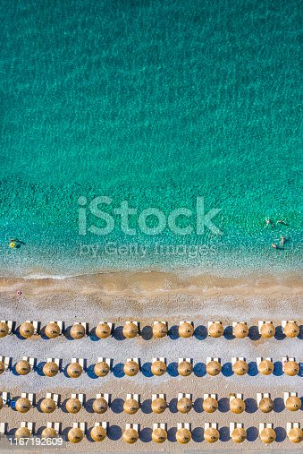 999001484 istock photo A couple of rows of sunbeds and umbrellas on a beach and an emerald sea, taken from air 1167192609