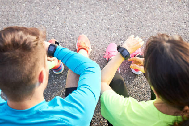 couple of runners sharing their racing data with their smart watches stock photo