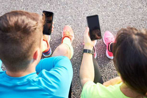 couple of runners sharing their running data with their mobile phones stock photo
