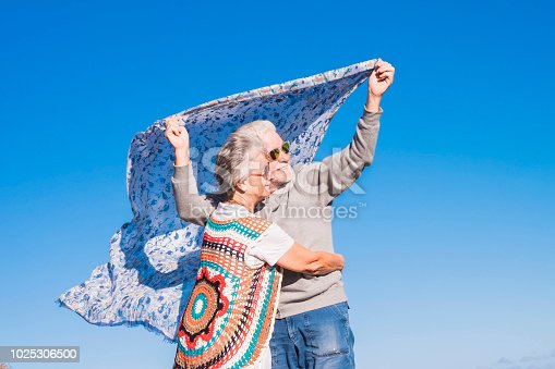 istock couple of senior caucasian hippy style and life rest on the rocky beach in Tenerife. colors and alternative lifestyle for totally freedom concept near the ocean. alternative colorful clothes to live free from the uses of the society. adult people happy 1025306500