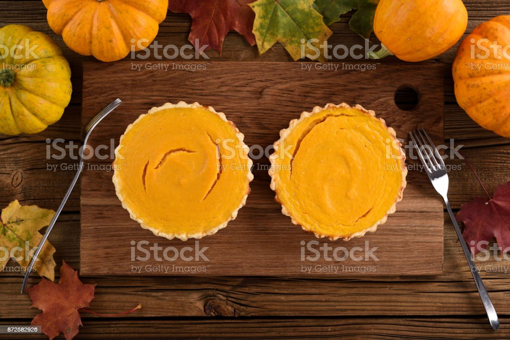 Couple of small traditional pumpkin pies on wooden board served with forks surrounded with pumpkins and marple leaves stock photo