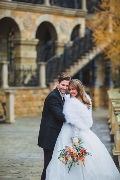 Couple of stylish newlyweds posing on the territory of country hotel stock photo