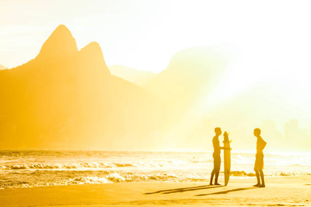 Couple of surfers chatting, one of them with the surfboard in hand, at the sunset of Ipanema, Rio de Janeiro, Brazil, on August 25, 2015 stock photo