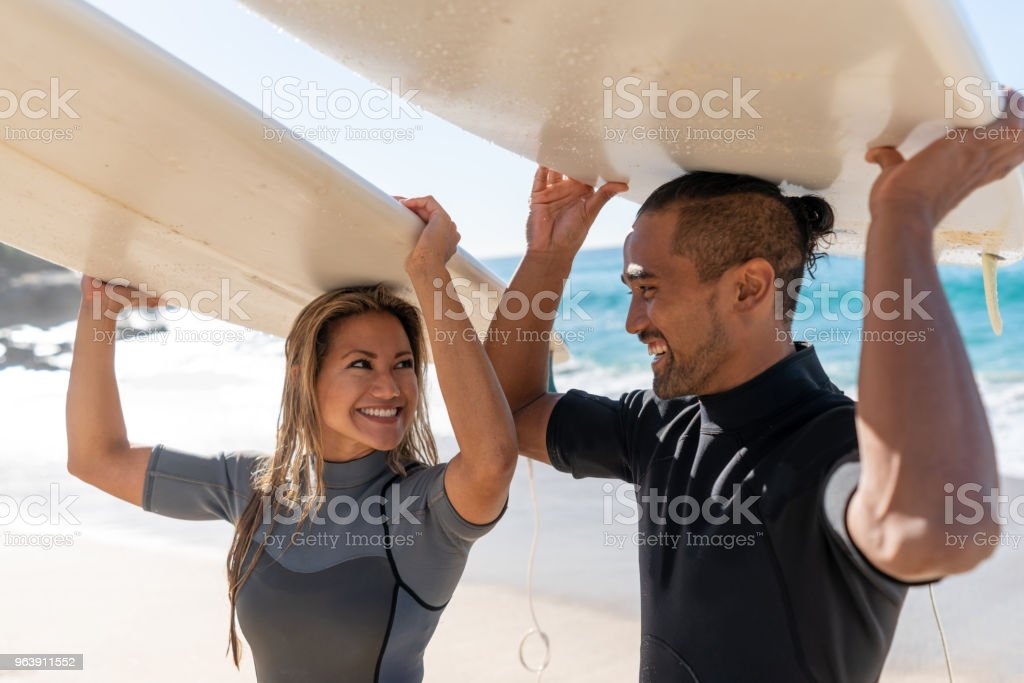 Couple of surfers looking happy at the beach - Royalty-free Adult Stock Photo