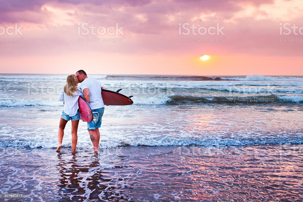 Couple of surfers walking on coast in Indonesia stock photo