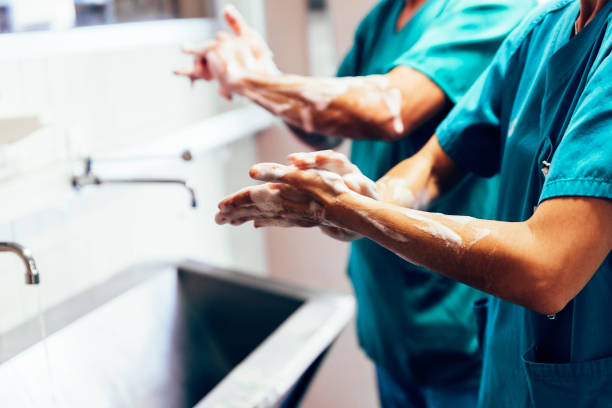couple of surgeons washing hands before operating. - infectious disease stock pictures, royalty-free photos & images