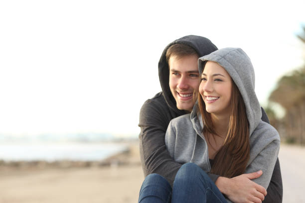 Couple of teens looking at horizon on the beach Happy couple of teens hugging and looking at horizon on the beach love at first sight stock pictures, royalty-free photos & images