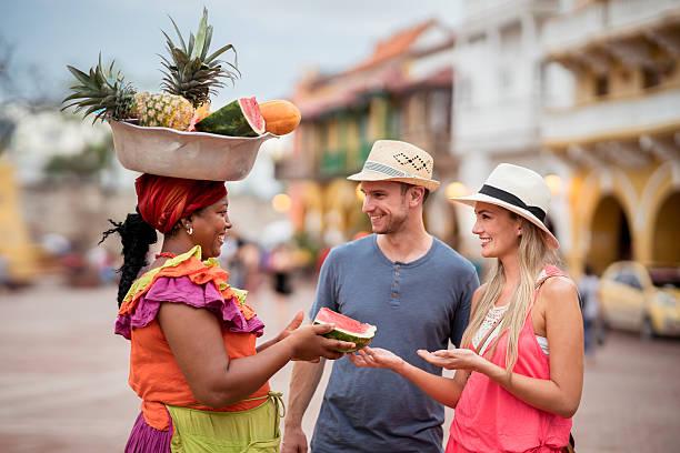 couple of tourist buying fruits in the street - viaje a sudamérica fotografías e imágenes de stock