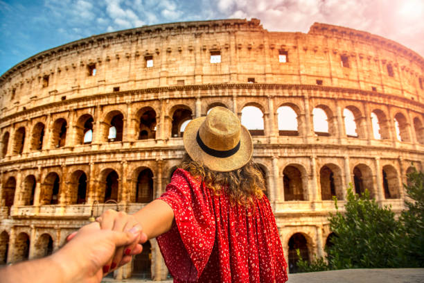 Couple of tourist on vacation in front of Colosseum Rome Italy Romantic woman and man holding hands and walking to Colosseum Rome, Italy. rome italy stock pictures, royalty-free photos & images