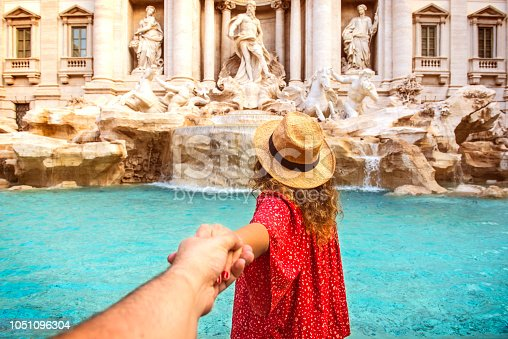 istock Couple of tourist on vacation in front of Trevi Fountain Italy 1051096304