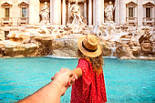 Romantic woman and man holding hands and walking to Trevi Fountain Rome, Italy.