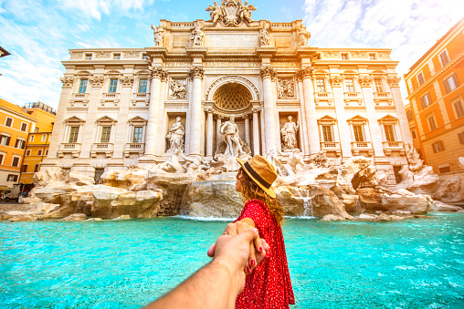Couple of tourist on vacation in front of Trevi Fountain Italy