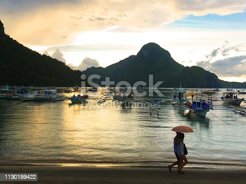 Backpacker tourist couple walking in front of the Ocean in El Nido, Port Barton, Palawan, Philippines