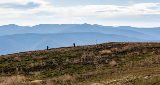 Bieszczady Dağları'nda işaretli iz boyunca bir gezi sırasında turist bir çift. Arka planda sisli ormanlık zirvelerde. stok fotoğrafı
